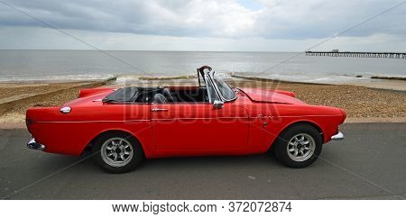 Felixstowe, Suffolk, England - May 05, 2019: Classic Red Sunbeam Tiger Convertible Car Parked On Sea
