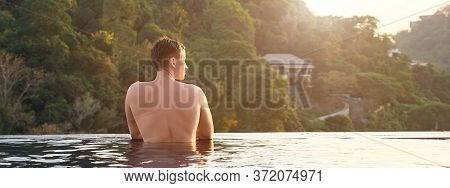 Man In Hotel Outdoor Swimming Pool Looking At Pictorial Tropical Forestry Hilly Landscape.
