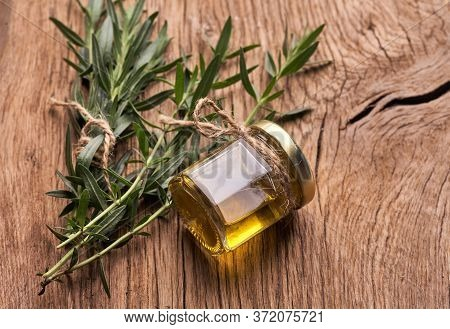 Top View Bottle Glass Of Essential Rosemary Oil With Rosemary Branch On Wooden Rustic Background.