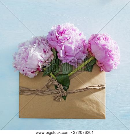 Pink Peonies Bouquet Closeup, Spring Flowers For Mother's Day In The Brown Envelope On Ligh Blue Woo