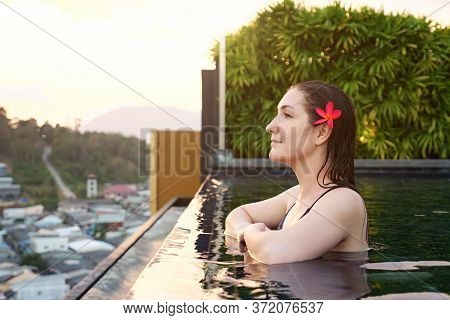 Beautiful Girl Enjoys Pictorial Landscape Standing In Outdoor Swimming Pool In Summer Evening Closeu