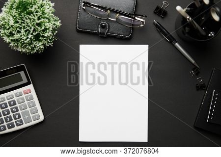 Top view of modern black office desk with blank paper sheet, notebook, pen and a lot of things. Flat lay table layout. Copy space for text.
