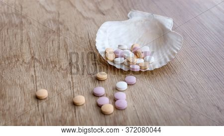 Tablets Of Calcium And Shell On A Wooden Table. Medical Concept. Minerals For Health. Top View.