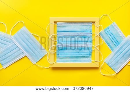 Medical Protective Face Masks On Yellow Pattern Texture Of Crumpled Paper With Yellow  Frame. Virus,