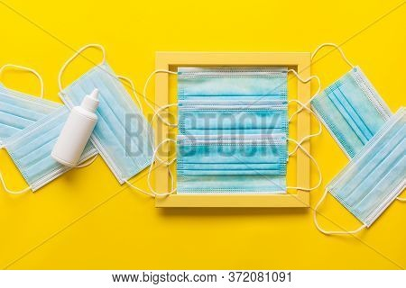 Medical Protective Face Masks With Hand Sanitizers On Yellow Paper With Yellow  Frame. Virus, Flu, C
