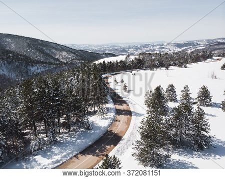 Winter Landscape In Sunlight. View On The Mountain Road Surrounded By Evergreen Trees In Winter, Dro