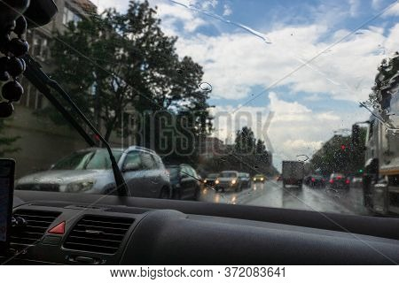 Traffic In Rainy Day With Road View Through Car Window With Rain Drops, Blurry Traffic On Rainy Day.