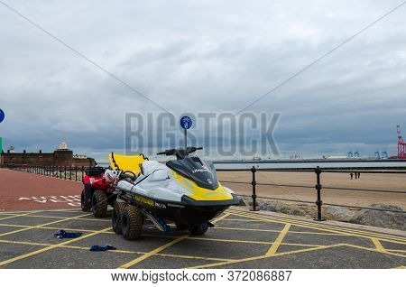 New Brighton, Uk: Jun 3, 2020: A Rnli Lifeguard  Jet-ski Is Seen On A Trailer Which Is Towed By A Qu