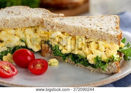 Egg Salad Sandwich With Lettuce On Whole Grain Bread And Grape Tomatoes On A Plate