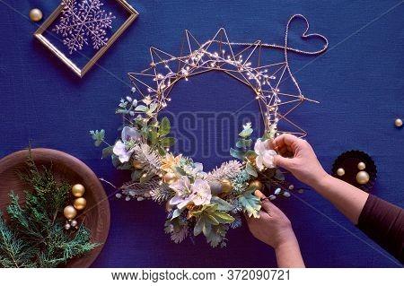 Making Of Decorative Christmas Wreath On Classic Blue Linen. Female Hands Make Handmade Wreath. Xmas