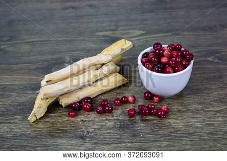 Cranberries In A White Cup, Horseradish Roots Spread Out On A Brown Wooden Table. Berries, Vegetable