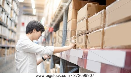 Young Asian Shopper Man Picking Cardboard Box Package From Product Shelf In Warehouse. Male Customer