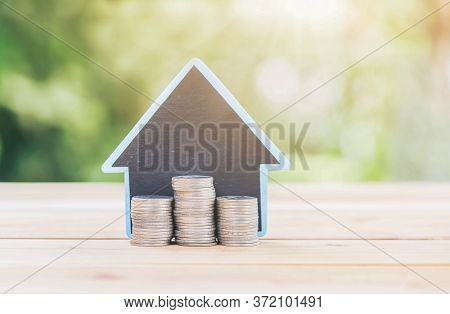 House Placed On The Table Silver Coins Placed A Piles. Planning Savings Money Of Coins To Buy A Home