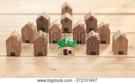 Green House In Among Wooden House For Real Estate. Planning Savings Money Of Coins To Buy A Home Con