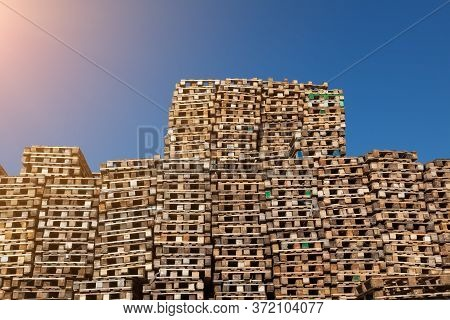 A Large Pile Of Used Wooden Pallets Stacked On Top Of Each Other Against A Blue Sky In The Sun For T
