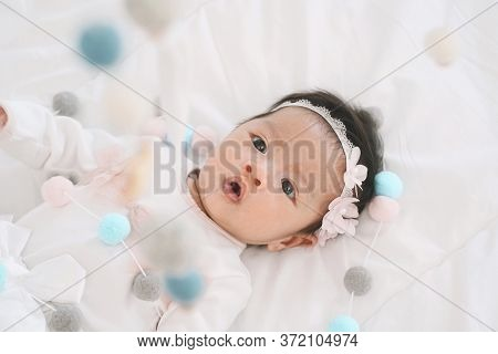 Adorable Little Baby Girl In A Beautiful Dress Watching Baby Crib Mobile At Home. Baby Crib Mobile.