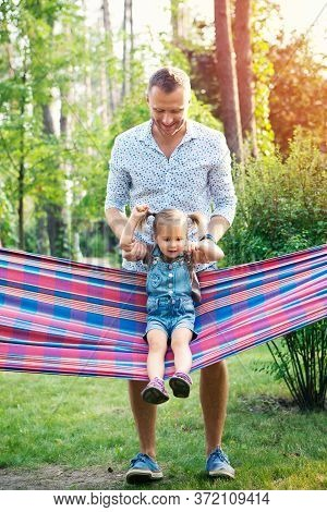Young Father With Two Kids Having Fun In Hammock. Father's Day, Family Day, Children's Day Concept