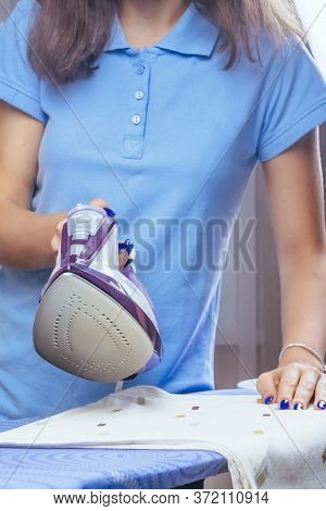 The Girl Holds An Iron On An Ironing Board With Ferry And Irons Things. Cleaning Service Of The Apar