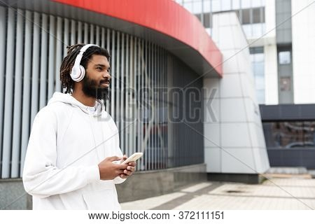 Image of a handsome concentrated young man walking outdoors while listening music by headphones and using mobile phone