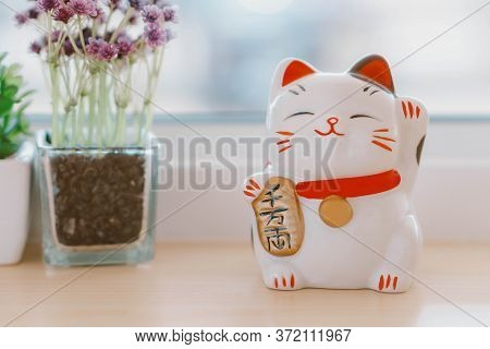 Maneki Neko Lucky Cat Show Text On Hand Meaning Rich On Table, Select Focus
