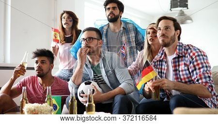 People, Leisure, Rivalry And Sport Concept. Happy And Sad Friends Or Fans Watching Match At Home