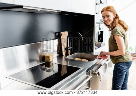 View Of Woman Smiling At Camera While Cleaning Kitchen Worktop With Rag