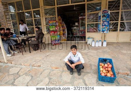 Kurdistan Province, Iran: Boy Smiling And Sitting Past Fruit Store And Cafe In Small Village On Octo