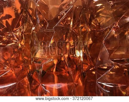 Amber Lights Shining Through Faceted Glass Wine Or Whiskey Bottles, Background Texture