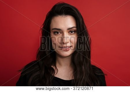 Photo of brunette nice woman in casual t-shirt posing and looking at camera isolated over red background