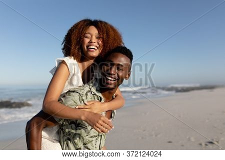 A mixed race couple enjoying free time on beach on a sunny day together, piggy backing and laughing with sun shining on their faces.
