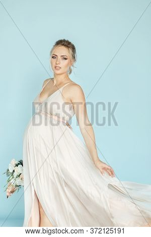 Pregnant Photo. Bride With Belly. Pregnant Bride With Flowers. Beautiful Young Blond Woman Expecting