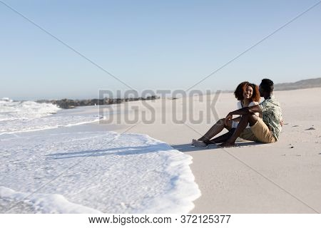 A mixed race couple enjoying free time on beach on a sunny day together, sitting on the sand and holding each other with sun shining on their faces.