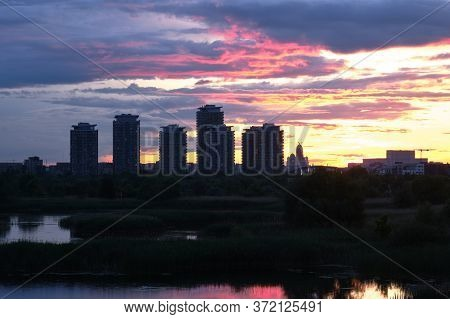 Bucharest City Skyline Seen From Vacaresti Park Nature Reserve At Sunset, With Skyscraper Towers And