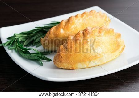 In The Field Of The Second Pie With Meat With A Sprig Of Greenery , Pies With Meat On A Plate