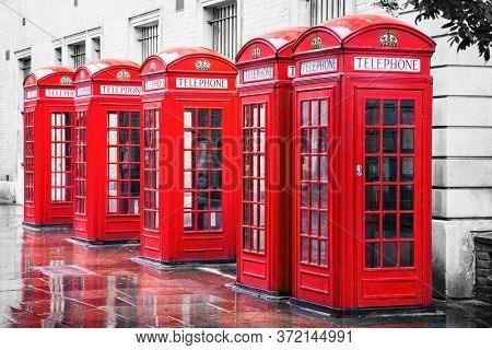 Traditional British red phone boxes in a row in Covent Garden, London. Colour removed from background to make the red stand out.