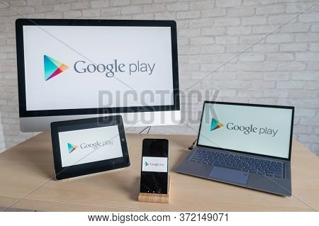 Google Play Logo On The Screens Of A Phone, Digital Tablet, Laptop And Computer. A Store Of Applicat