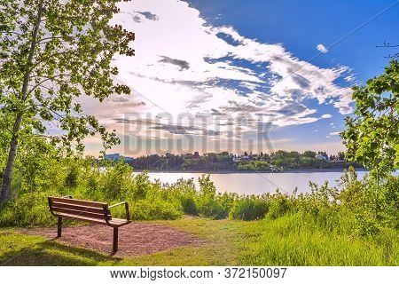 A Scenic Bench Overlooking A Spring Park