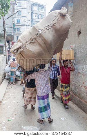 Dhaka, Bangladesh - November 22, 2016: Local Worker Carries A Bulky Bag In Old Dhaka, Bangladesh