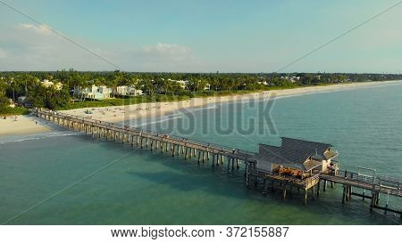 Pier In Naples By Aerial Drone. Drone Flies Around A Fishing Pier In Naples, Florida Usa. Coast And