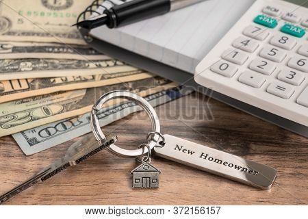 house key with office supplies on wooden desk.