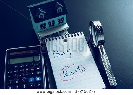 buy or rent question  on note with office supplies on desk.