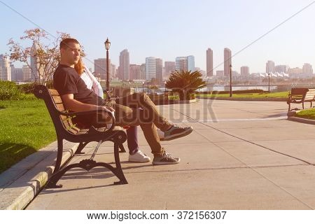 Couple Relaxing On San Diego City Bench. Young Adult Couple Laughing, Sit In A Bench. Young Adult Co