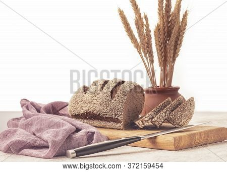 Rye Bread Sliced On A Wooden Board With A Bundle Of Wheat