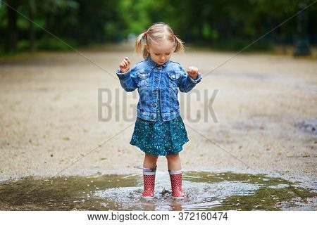 Child Wearing Red Rain Boots And Jumping In Puddle On A Summer Day. Adorable Toddler Girl Having Fun