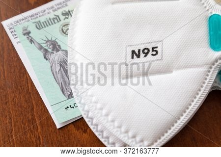 N95 Medical Face Mask Resting On IRS Covid-19 Economic Relief Check