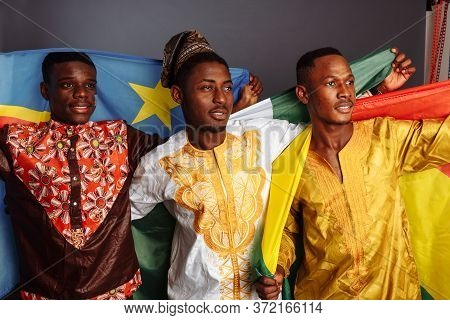 Concept Of Friendship Between African Countries: 3 African Men In National Clothes From Different Co