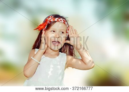 Happy Kid Girl Hand To Ear Eavesdropping Trying To Hear A Chitchat. Closeup Portrait Of Caucasian Ki