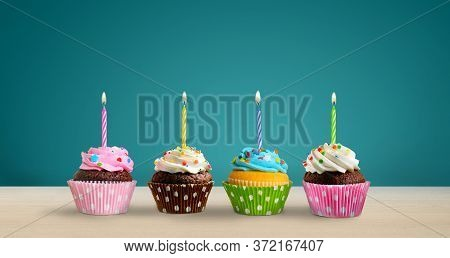 Row Of Colorful Birthday Cupcakes With Burning Candles On The Table. Copy Space