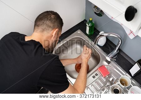 Cleaning Blocked Drain Clog In Kitchen Sink Using Plunger