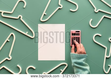 White Plastic Hangers, Hand With Calculator And White Page With Copy-space. Creative Top View Flat L